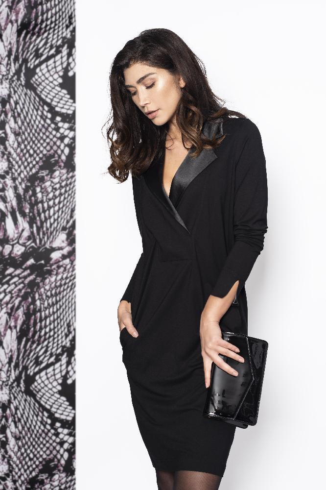 Deze Dress chique heeft een zeer luxe uitstraling door de hoge kwaliteit stof, de reverskraag en afwerking met satijn. De jurk valt tot op de knie, heeft lange mouwen met splitjes onderaan.  Materiaal: Viscose, Satijn, Elastaan